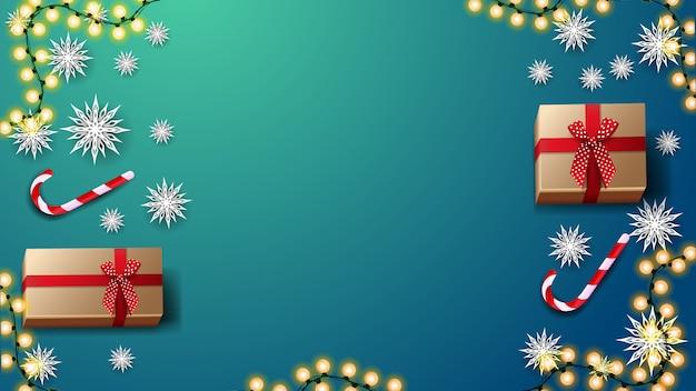 Geschenken, candys suikerriet, papier sneeuwvlokken en garland op blauwe tafel, bovenaanzicht. achtergrond Premium Vector