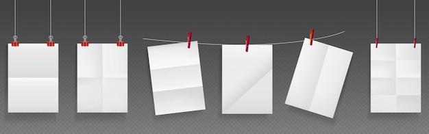 Gevouwen papier hangt aan touw en spelden, witte papieren blanco vellen met gekreukelde textuur. Gratis Vector