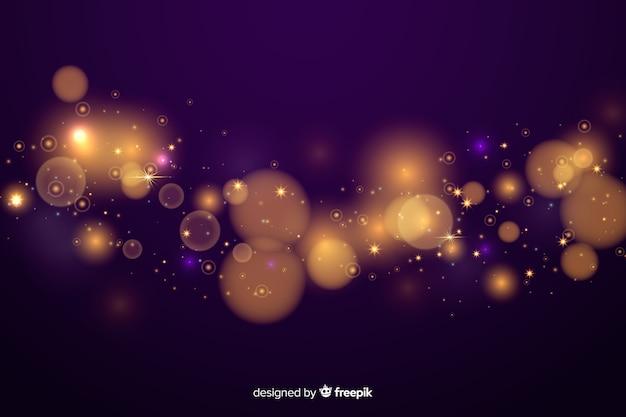 Gouden deeltjes bokeh decoratieve achtergrond Gratis Vector