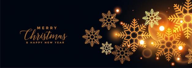 Gouden sneeuwvlokken op zwarte vrolijke kerstmisbanner Gratis Vector