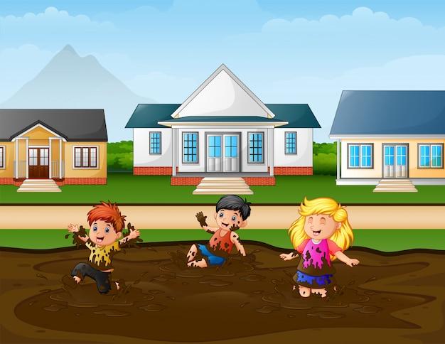 Grappige kinderen die een moddervulklei in de landelijke scène spelen Premium Vector