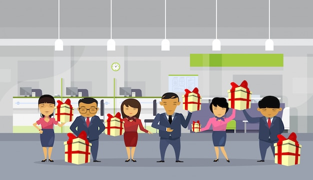 Groep aziatische zakenmensen houden geschenk dozen in moderne kantoor Premium Vector