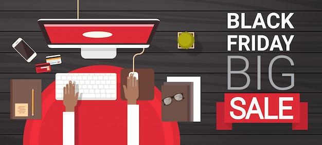 Groot de verkoopteken van black friday over het typen op computerdesktop boven de bannerconcept van de meningsvakantie Premium Vector