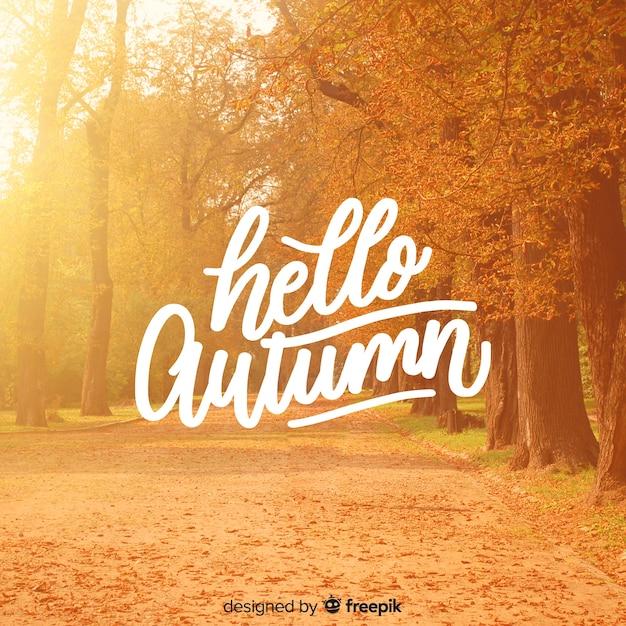 Hallo herfst belettering achtergrond met foto Gratis Vector