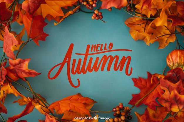 Hallo herfst belettering achtergrond met realistische bladeren Gratis Vector