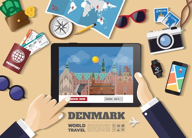 Hand die slimme tablet het boeken reisbestemming houden denemarken beroemde plaatsen Premium Vector