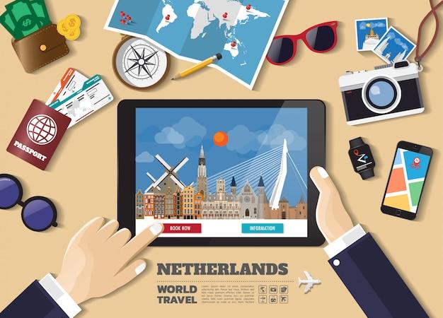 Hand die slimme tablet het boeken reisbestemming houdt. nederlandse bekende plaatsen Premium Vector