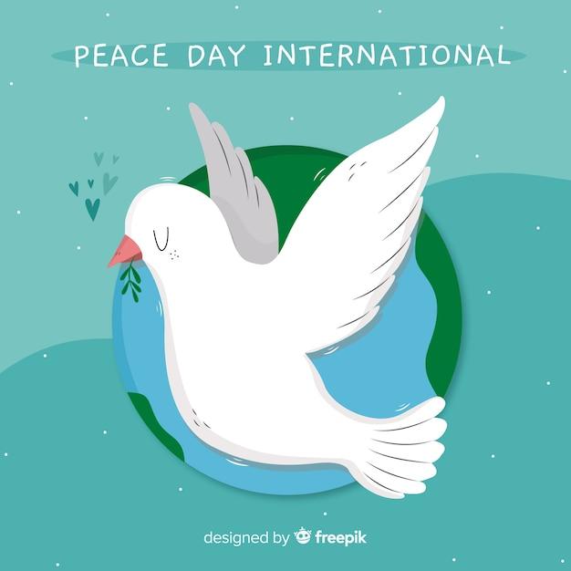 Hand getekend vredesdag duif met wereld Gratis Vector
