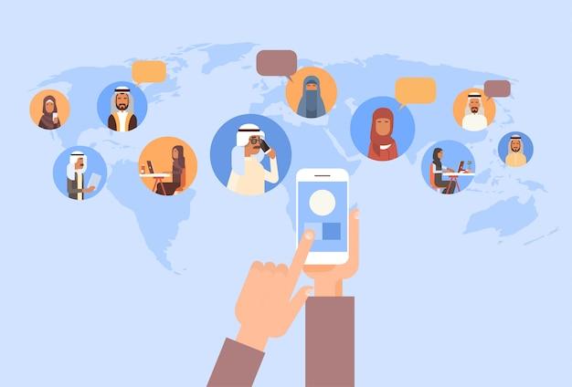 Hand met behulp van mobiele slimme telefoon, islamitische mensen chat media communicatie sociaal netwerk arabische mannen en wo Premium Vector