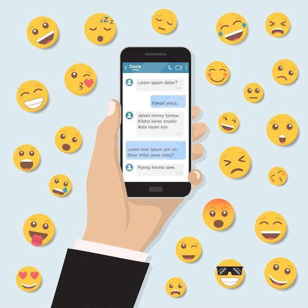 Hand met smartphone met chatberichten en emoticon in een plat ontwerp Premium Vector
