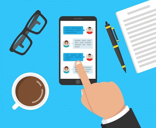 Hand met telefoon met berichten op het scherm Premium Vector