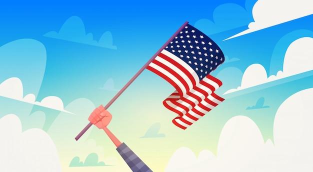 Hand met usa vlag over blauwe hemel nationale patriot dag verenigde staten vakantie banner Premium Vector