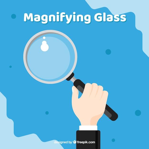 Hand met vergrootglas in vlakke stijl Gratis Vector