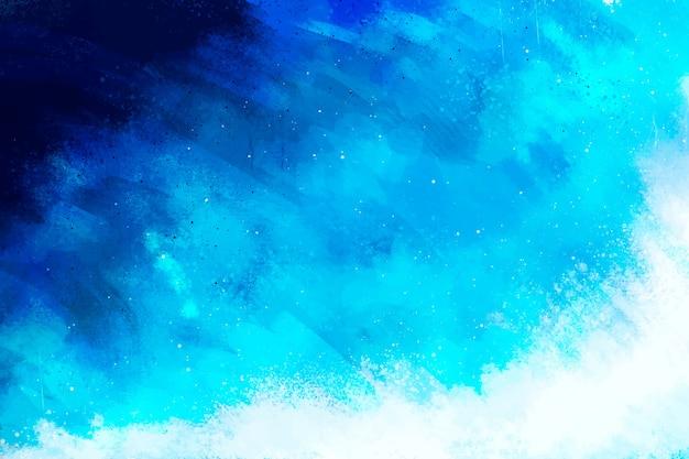 Handgeschilderde achtergrond in kleurovergang blauw Gratis Vector