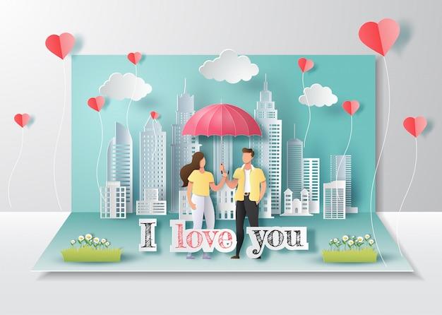 Happy valentine's day, pop-up kaart, schattig paar in liefde houden paraplu met stad. Premium Vector