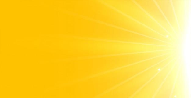 Helder gele achtergrond met gloeiende stralen licht Gratis Vector
