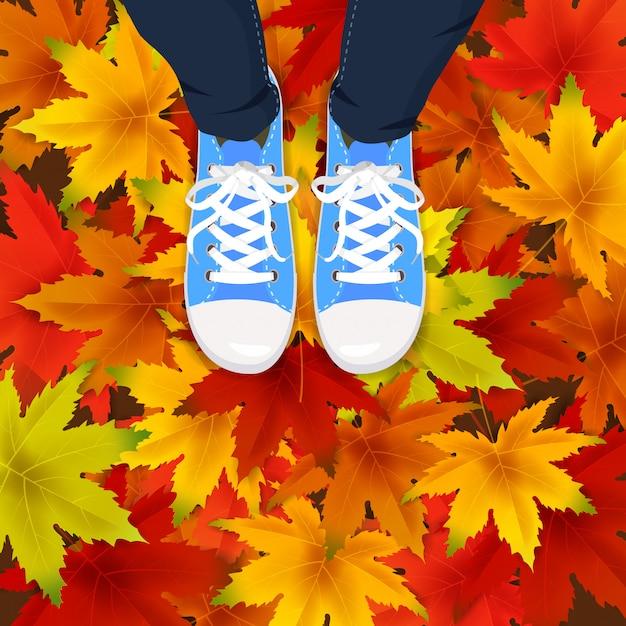 Herfstbladeren achtergrond sjabloon met esdoorn bladeren benen bovenaanzicht in schoenen sneakers op kleurrijke vallende bladeren. Premium Vector