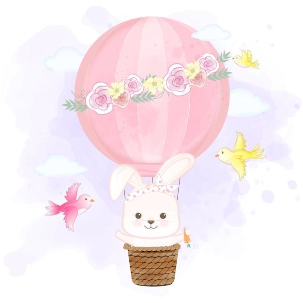 Het leuke konijn die op hete luchtballon drijven en vogels overhandigt getrokken beeldverhaalillustratie Premium Vector