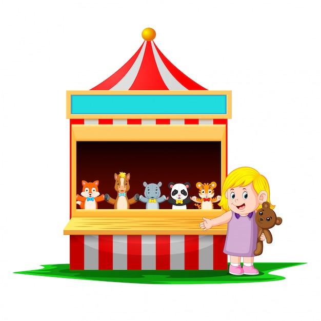 Het meisje op het carnaval met de teddybeer is heel grappig Premium Vector