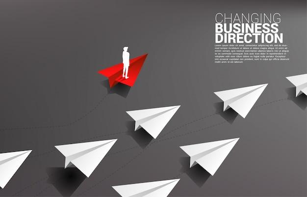 Het silhouet die van zakenman zich op rood origamidocument vliegtuig bevinden is beweging apart van groep wit. bedrijfsconcept verstoring en nichemarketing Premium Vector