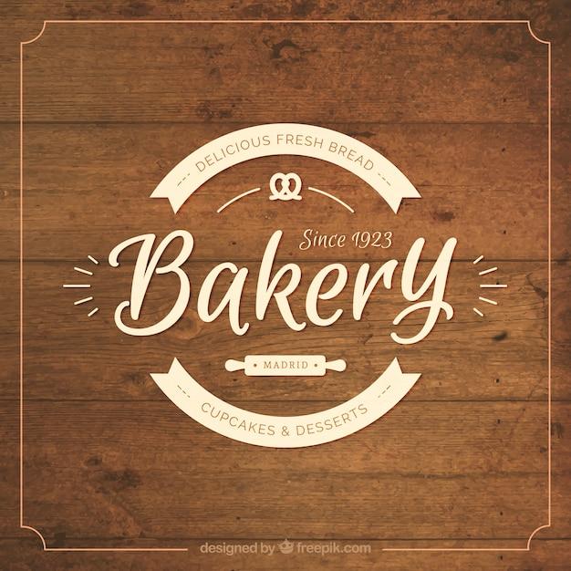 Houten achtergrond met bakkerij badge Gratis Vector