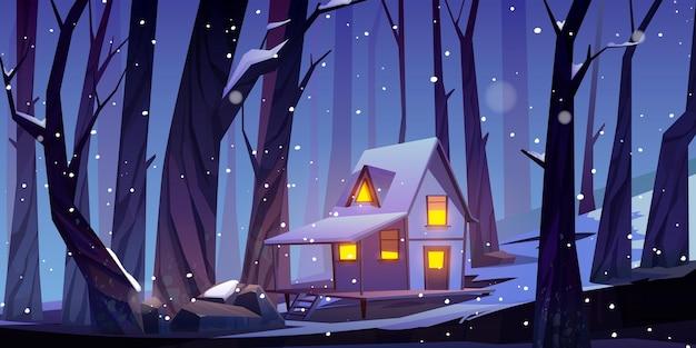 Houten huis in de winter woud 's nachts. boswachterhut met glimmende ramen en witte sneeuw op het dak. Gratis Vector