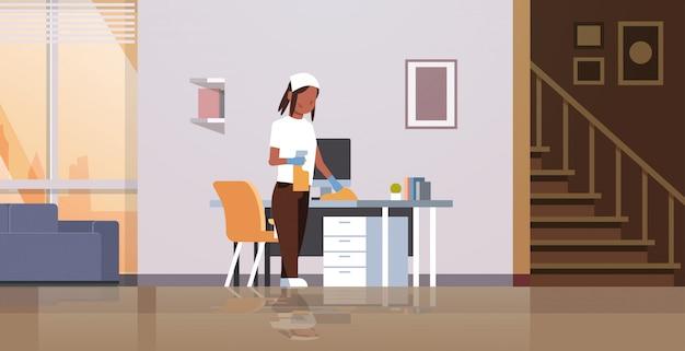 Huisvrouw schoonmaken computertafel met stofdoek vrouw afvegen werkplek bureau huishoudelijk werk concept moderne woonkamer interieur vrouwelijke stripfiguur volledige lengte horizontaal Premium Vector