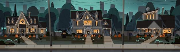 Huizen ingericht voor halloween, s vooraanzicht met verschillende pompoenen Premium Vector