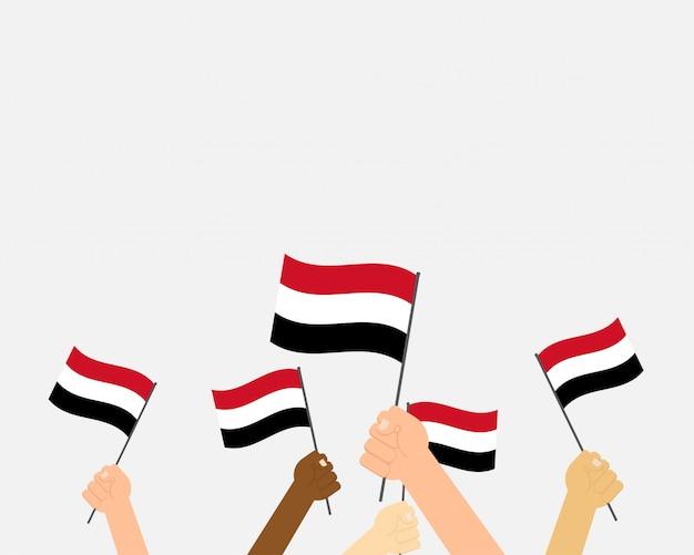 Illustratie handen met jemen vlaggen Premium Vector