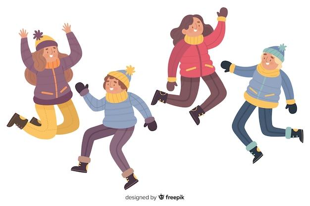 Illustratie van jongeren die terwijl het dragen van de winterkleren springen Gratis Vector