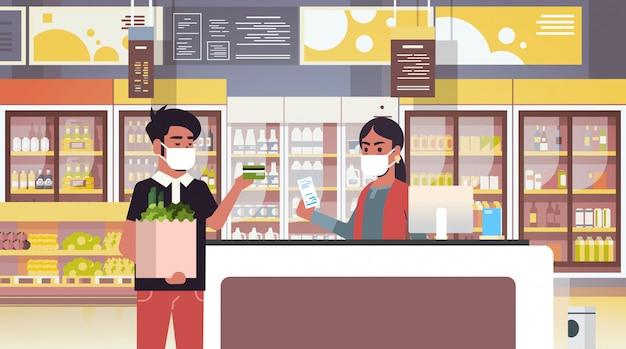 Indiase kassier en man klant in medische beschermende maskers quarantaine coronavirus epidemie concept mensen kopen van goederen in supermarkt supermarkt interieur portret horizontaal Premium Vector