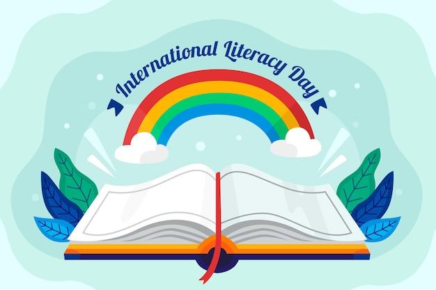 Internationale alfabetiseringsdag met open boek en regenboog Gratis Vector