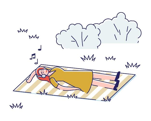 Jong meisje luisteren naar muziek liggend op een deken in het park. Premium Vector