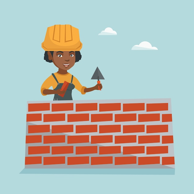 Jonge afrikaanse metselaar die een bakstenen muur bouwt. Premium Vector