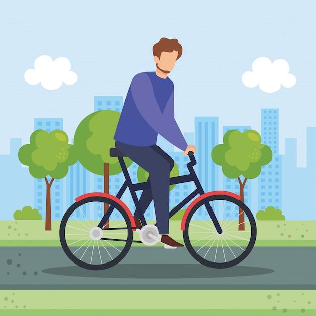 Jonge man in fiets in het park Gratis Vector