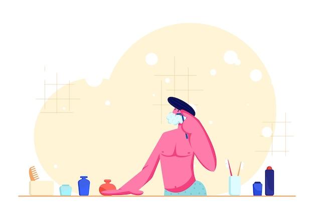 Jonge man met blote torso scheren in badkamer scheermes voor baard doorgeven terwijl kijken naar spiegel Premium Vector