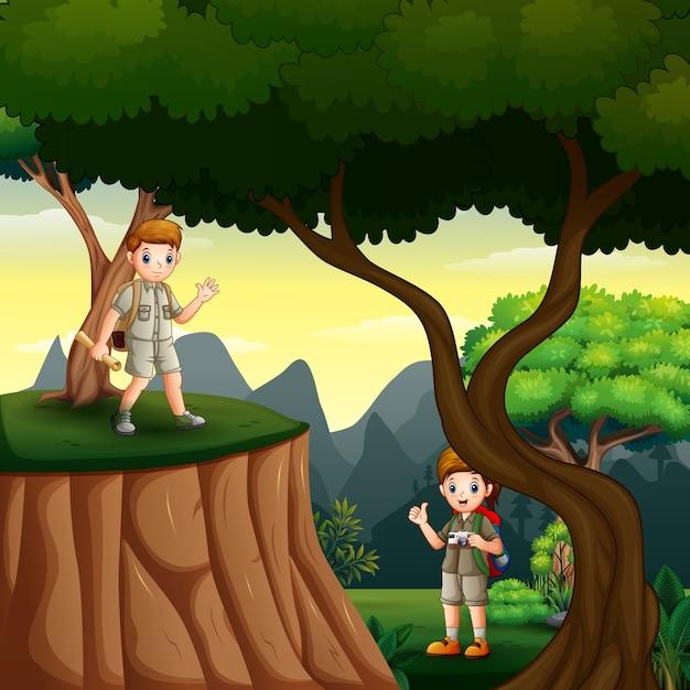Jonge scouts wandelen in het boslandschap Premium Vector