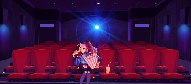 Jonge vrouw in de bioscoop betoverd meisje met popcornemmer in handen die alleen in bioscoop zitten Gratis Vector