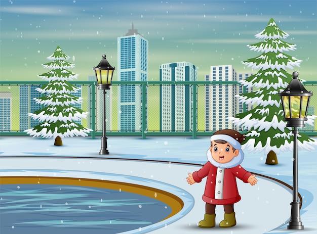 Jongen die warm jasje en hoed in het park draagt Premium Vector