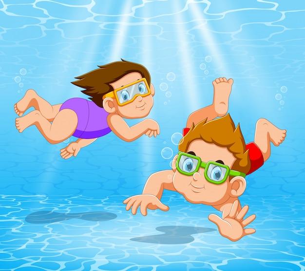 Jongen en meisje spelen en zwemmen in het zwembad onder het water Premium Vector