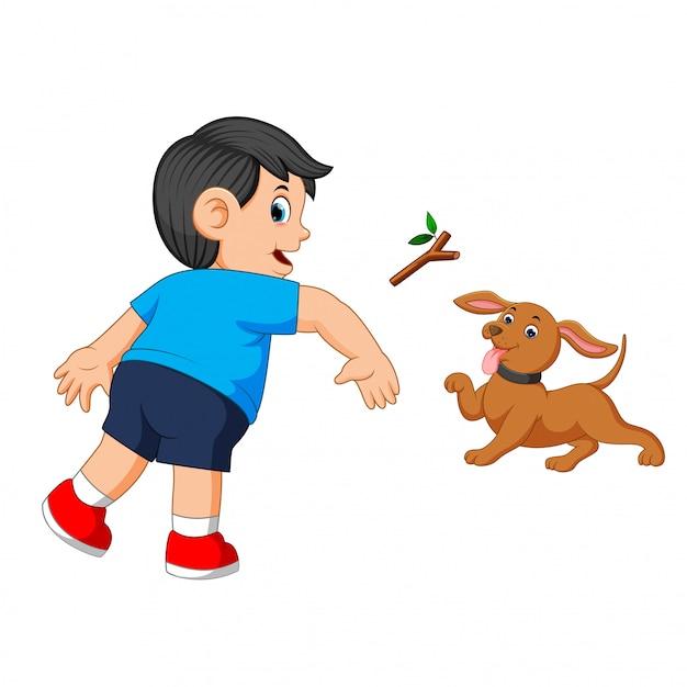 Jongen gooit een stok naar zijn hond Premium Vector