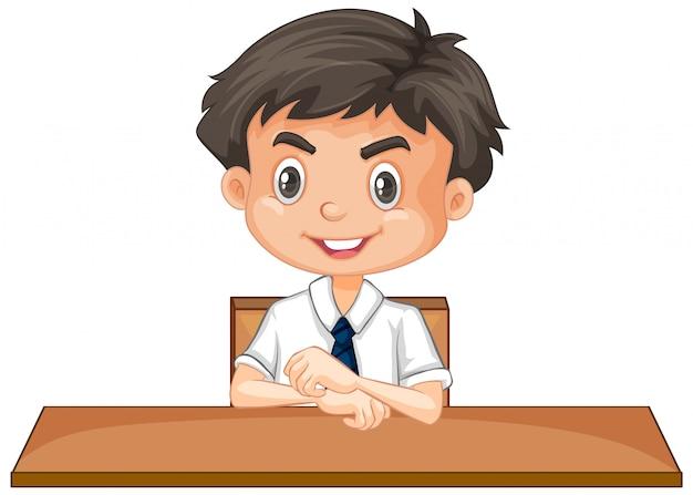 Jongen in school eenvormige zitting bij bureau op wit Gratis Vector