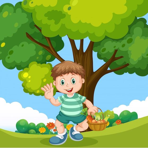 Jongen met plantaardige mand in het park Gratis Vector