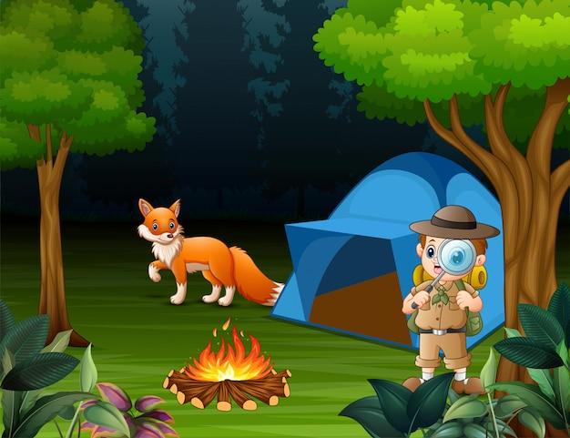 Jongensverkenner die in het bos en een vos dichtbij de tent kampeert Premium Vector