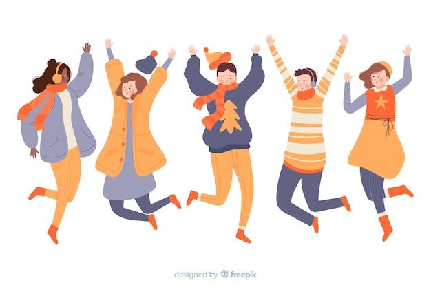 Jongeren springen tijdens het dragen van winterkleren Gratis Vector