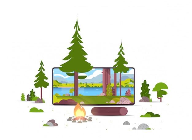 Kampvuur in het wild zomer bos prachtige rivier bergen landschap natuur toerisme kamperen of wandelen concept smartphone scherm online mobiele applicatie Premium Vector