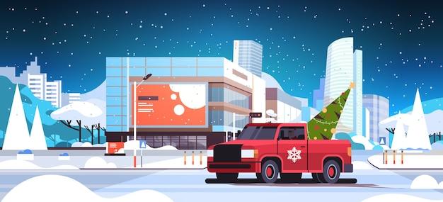 Kerstman rijden rode pick-up auto met dennenboom vrolijk kerstfeest winter vakantie viering concept moderne stad straat besneeuwde stadsgezicht horizontale platte vectorillustratie Premium Vector