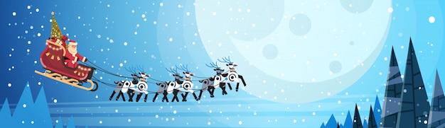 Kerstman vliegt in slee met rendieren nachtelijke hemel over maan voor kerstmis Premium Vector