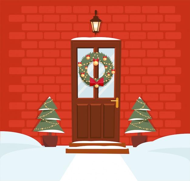 Kerstmis bruine deur met kroon, sneeuw en sparren op rode bakstenen muur. gesmede lantaarn boven de deur schijnt. Premium Vector