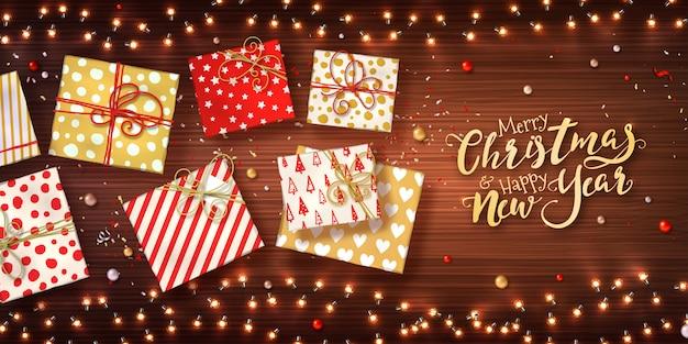 Kerstmis en nieuwjaar achtergrond met geschenkdozen, xmas slingers van lichten, kerstballen en glitter confetti op houten textuur. Premium Vector